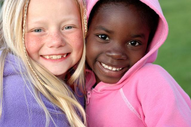 two young girls facing forward smiling I children's dentist Decatur IL