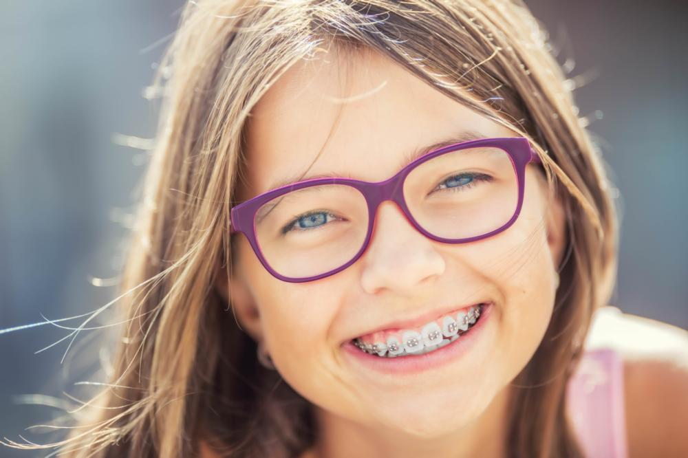 young girl with glasses smiling brightly with braces I jerger pediatric dentistry
