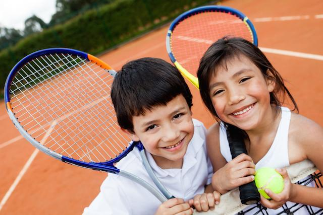 two children smiling playing tennis I pediatric dentistry in decatur il