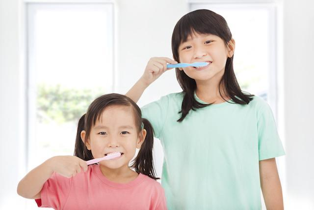two young girls brushing teeth with toothpaste I jerger pediatric dentistry in decatur il