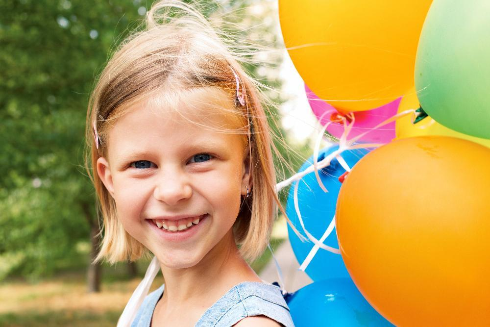 young girl smiling with balloon l dental cleanings decatur il