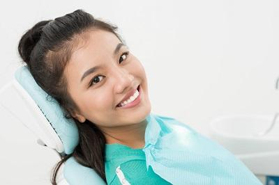 woman smiling in dental exam chair l orthodonics decatur il