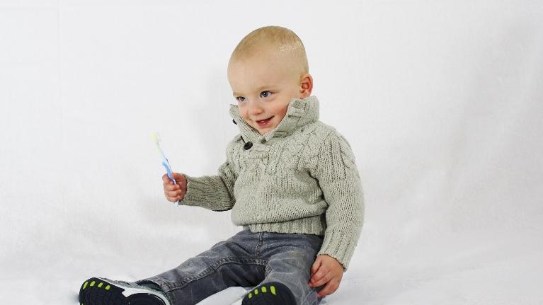child sitting with a toothbrush