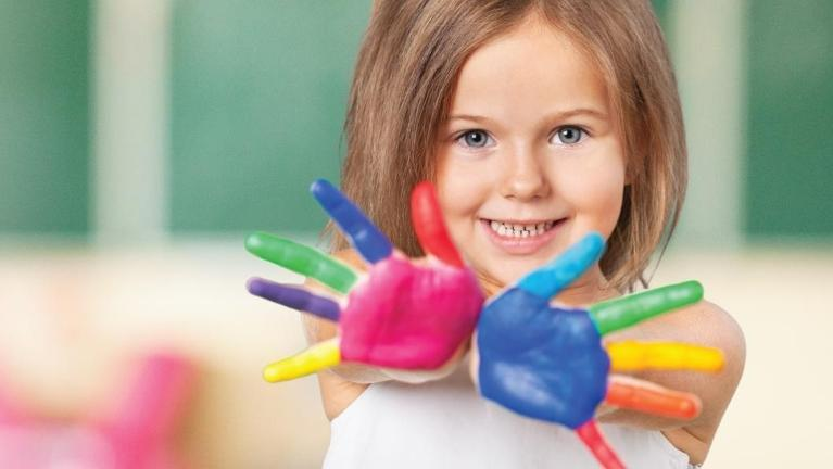 Young girl with paint on her hands l Jerger Pediatric Dentistry